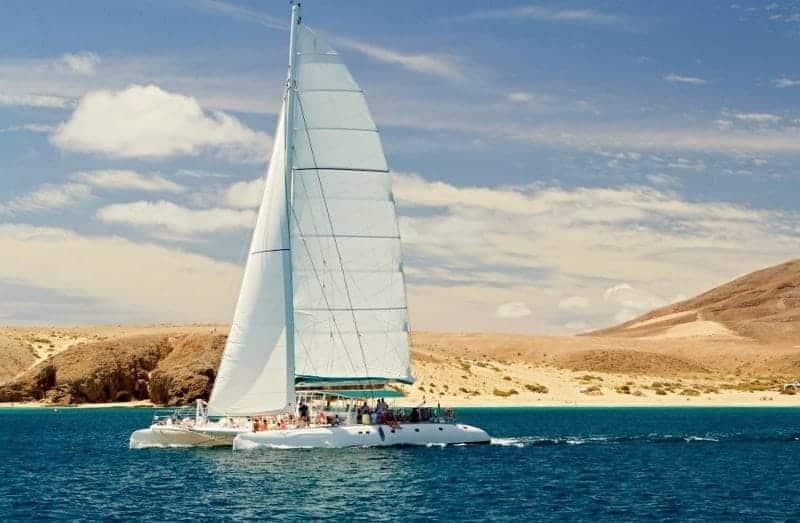 Catamarán con la vela izada frente a la Playa de Papagayo