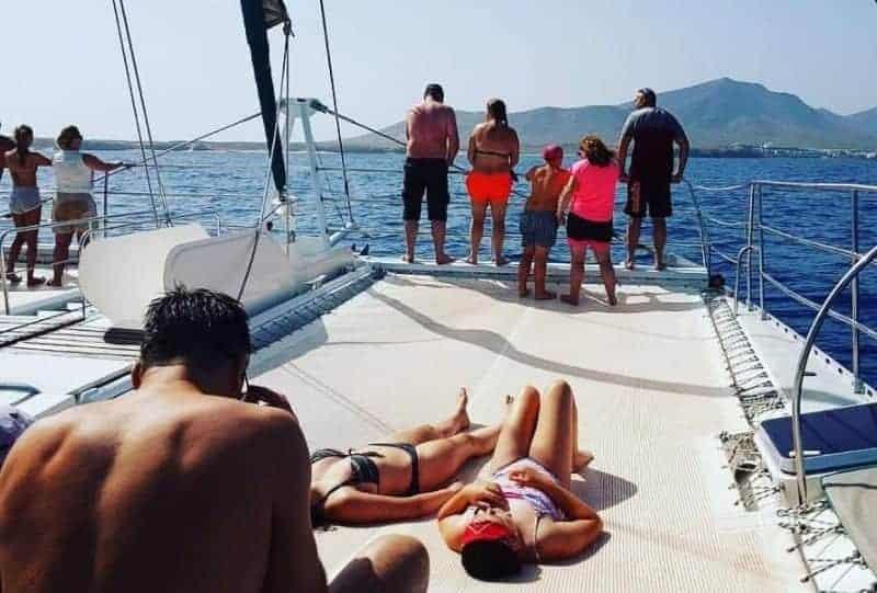 Touristen, die auf dem Deck ein Sonnenbad nehmen